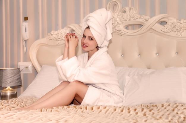 Fille d'apparence slave en blouse blanche sur le lit dans la chambre d'hôtel