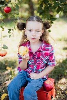 Fille avec apple dans le verger de pommiers