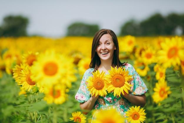 La fille applique des fleurs de tournesol sur sa poitrine