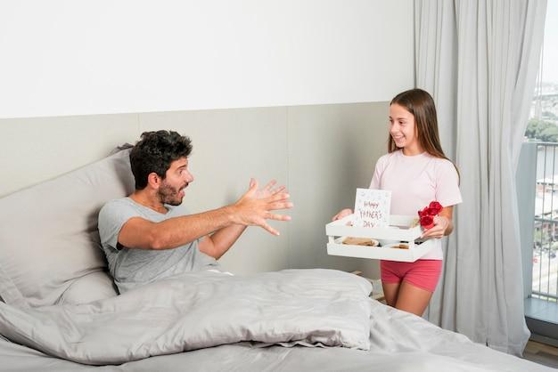 Fille apporte le petit déjeuner le jour de la fête des pères
