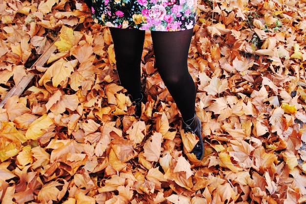 Fille appréciant les feuilles d'automne