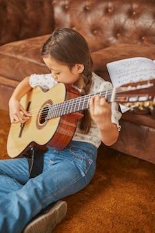 Fille apprenant à jouer de la guitare à la maison