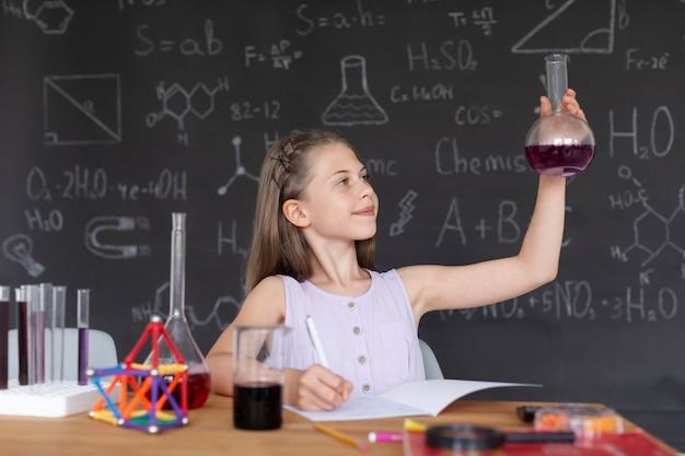 Fille apprenant plus sur la chimie en classe