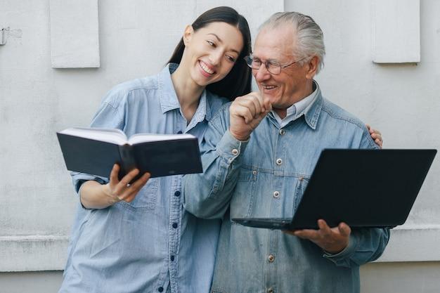 Fille apprenant à son grand-père comment utiliser un ordinateur portable