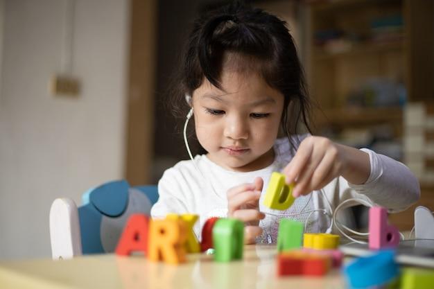Fille apprend en ligne à la maison avec des jouets