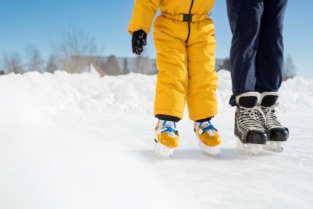 Une fille apprend à patiner avec son père par une journée ensoleillée à la patinoire de la ville