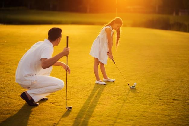 Fille apprend à prendre une balle de golf en regardant un père.