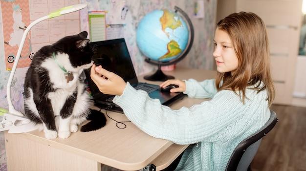 Fille d'apprentissage à distance caressant un chat à la maison