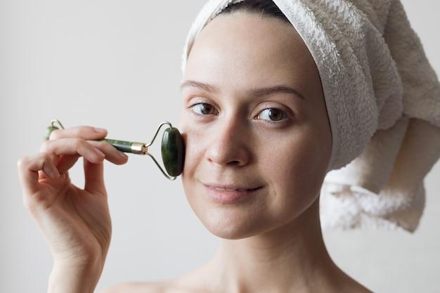 Une fille après une douche avec une serviette sur la tête fait un massage du visage avec un masseur de jade. photo de haute qualité