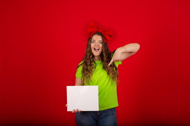 Fille avec un arc rouge la tête dans un t-shirt vert clair en jean bleu tient une feuille de papier blanc