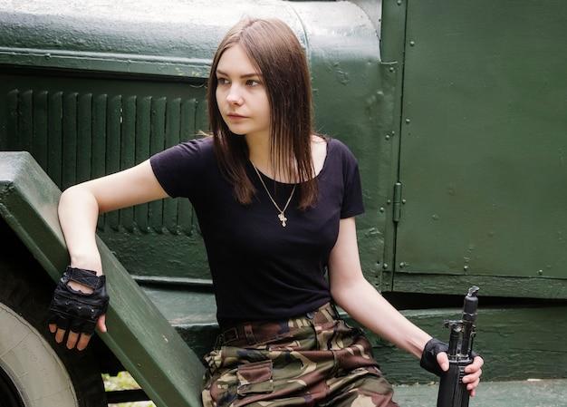 Fille avec une arme à feu assise sur les marches du camion de l'armée
