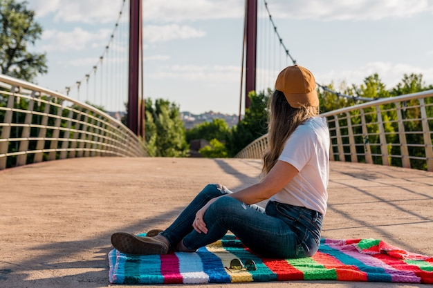 Fille avec une armoire dorée assise au milieu du pont rouge. couverture arc-en-ciel multicolore. berge de rivière. concept de mode de vie.