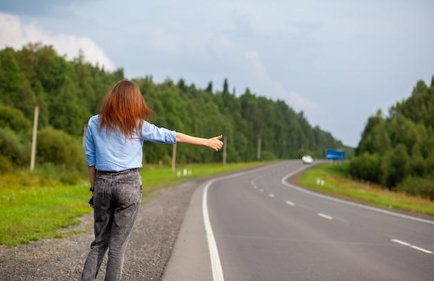 La fille arrête la voiture sur l'autoroute avec sa main. une femme élégante sur la route arrête la voiture pour un voyage. une route au milieu de la forêt.