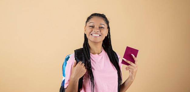La fille à l'arrière-plan jaune tient le passeport et le sac à dos