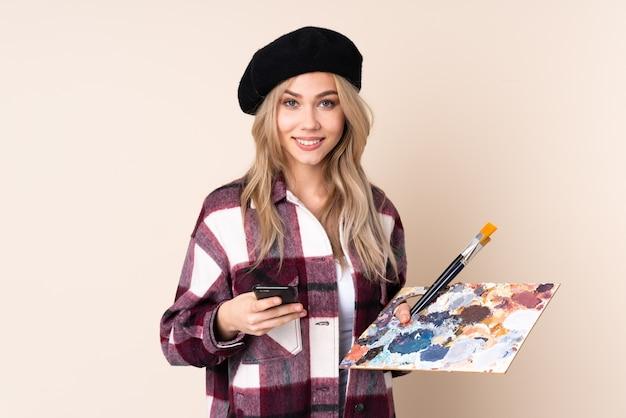 Fille artiste adolescent tenant une palette isolée sur bleu envoi d'un message avec le mobile
