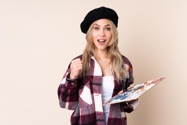 Fille artiste adolescent tenant une palette sur le mur bleu célébrant une victoire en position de gagnant