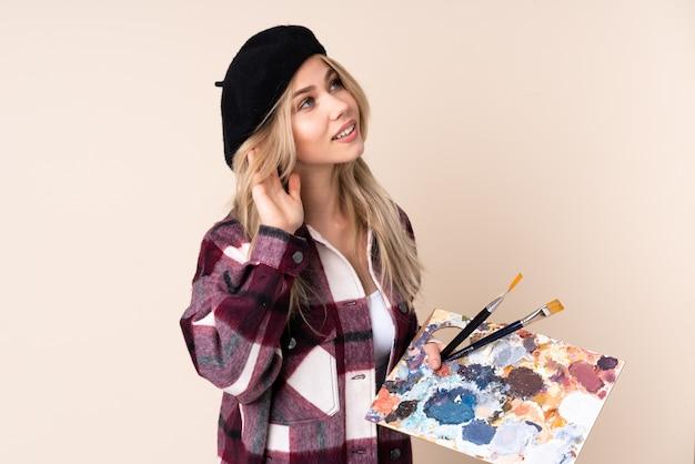 Fille artiste adolescent tenant une palette sur le mur bleu en écoutant quelque chose en mettant la main sur l'oreille