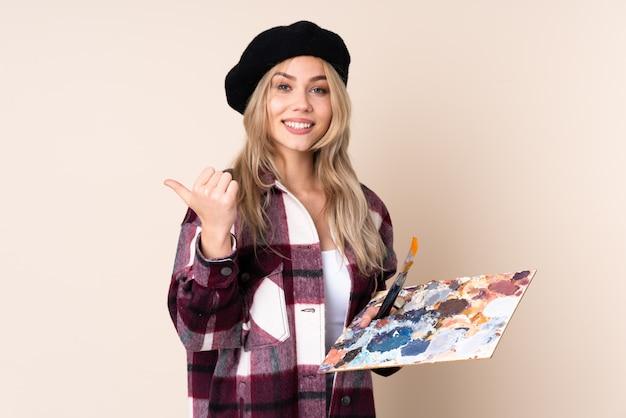 Fille artiste adolescent tenant une palette sur le mur bleu avec le geste du pouce en l'air et souriant