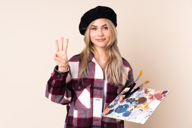 Fille artiste adolescent tenant une palette sur le mur bleu heureux et en comptant trois avec les doigts