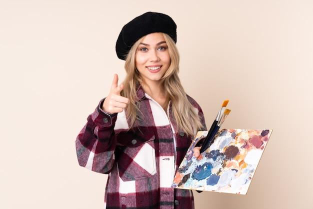 Fille artiste adolescent tenant une palette sur le mur bleu pointant vers l'avant et souriant