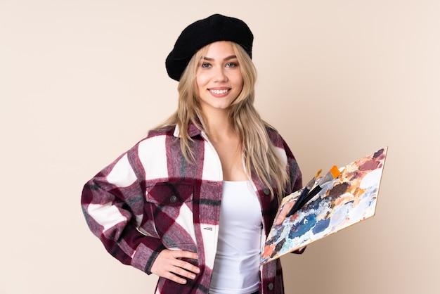 Fille artiste adolescent tenant une palette sur le mur bleu posant avec les bras à la hanche et souriant