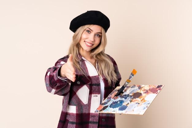 Fille artiste adolescent tenant une palette sur le mur bleu se serrant la main
