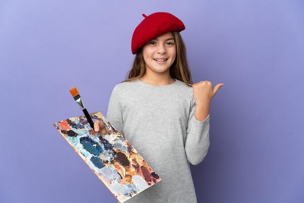 Fille d'artiste sur fond isolé pointant sur le côté pour présenter un produit