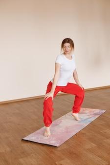 Fille en asana fait du yoga à la maison