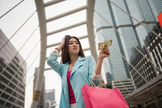 Fille asiatique accro du shopping triste