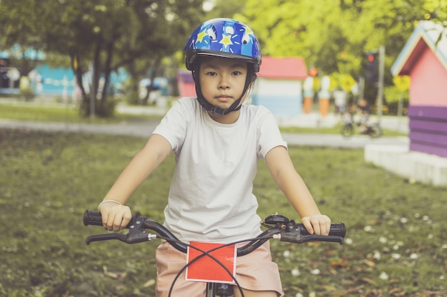 Fille asiatique apprend à faire du vélo dans le parc. portrait d'un enfant mignon à vélo.