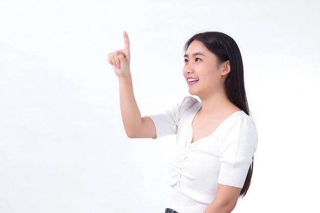 Une fille asiatique aux cheveux longs noirs porte une chemise blanche et pointe sa main pour présenter quelque chose