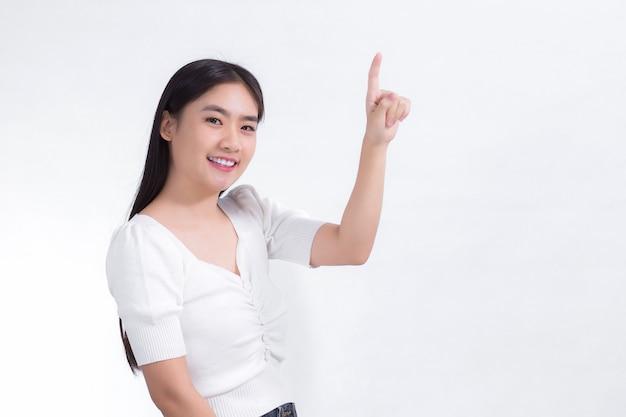 Une fille asiatique aux cheveux longs noirs porte un sourire de chemise blanche et pointe sa main pour présenter quelque chose