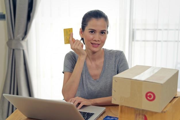 Fille asiatique belle achat en ligne à partir du site web en utilisant la carte de crédit pour le paiement.