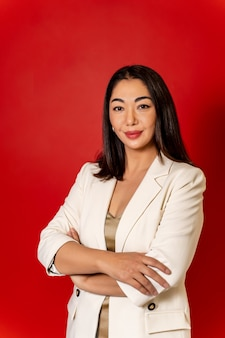 Fille asiatique de belle entreprise en veste blanche sur fond rouge.