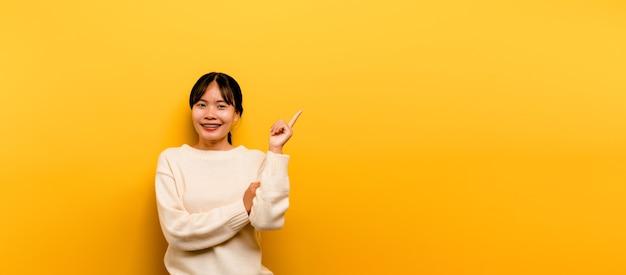 Fille asiatique belle vêtue d'une robe décontractée blanche sur fond jaune. célébrez la victoire avec un sourire joyeux et l'expression du vainqueur avec une main levée. expression heureuse