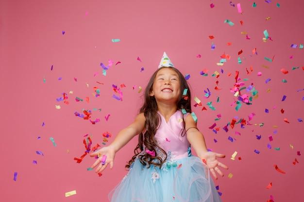 Une fille asiatique célèbre les coups d'anniversaire attrape des confettis sur le rose