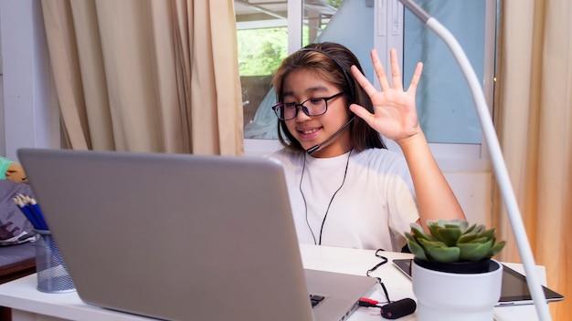 Une fille asiatique dans des écouteurs s'assoit au bureau pour étudier en ligne sur un ordinateur portable un enfant porte un casque d'apprentissage en utilisant des cours sur internet en quarantaine étudiant apprenant un cours en ligne virtuel sur internet depuis l'école en raison de covid19