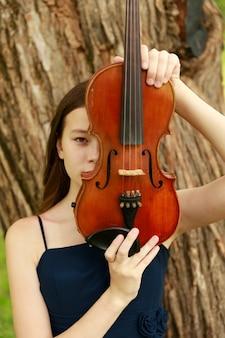 Fille asiatique dans la nature avec violon. photo de haute qualité