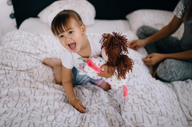 Fille asiatique drôle jouant avec une poupée à la maison