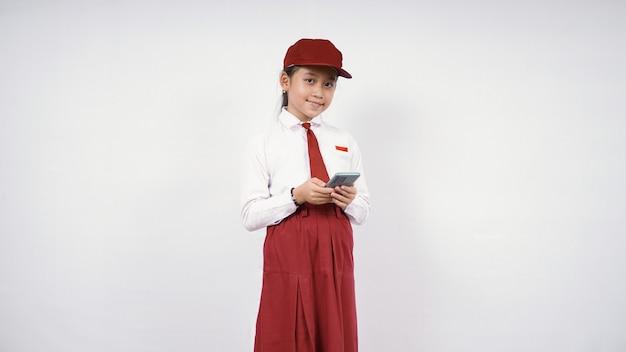 Fille asiatique de l'école primaire jouant le smartphone heureusement d'isolement sur le fond blanc