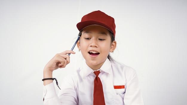 Une fille asiatique de l'école primaire trouve une idée intéressante isolée sur fond blanc