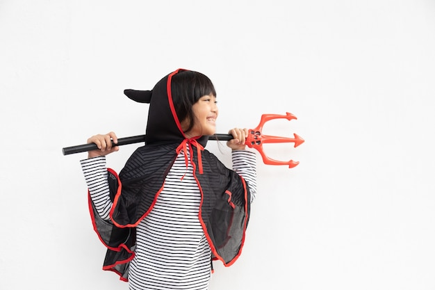Fille asiatique d'enfant dans le costume de démon tenant le trident noir et rouge, concept heureux d'halloween