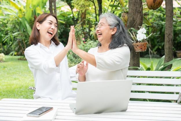 Fille asiatique enseignant à une vieille femme âgée utiliser les médias sociaux en ligne dans un ordinateur portable après la retraite. concept de technologie d'apprentissage et d'adaptation des personnes âgées