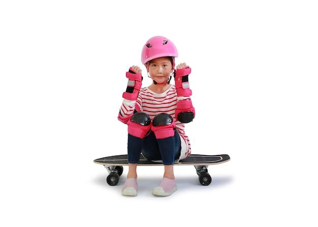 Une fille asiatique avec un équipement de protection lève les mains pour un geste fort s'asseoir sur une planche à roulettes sur blanc