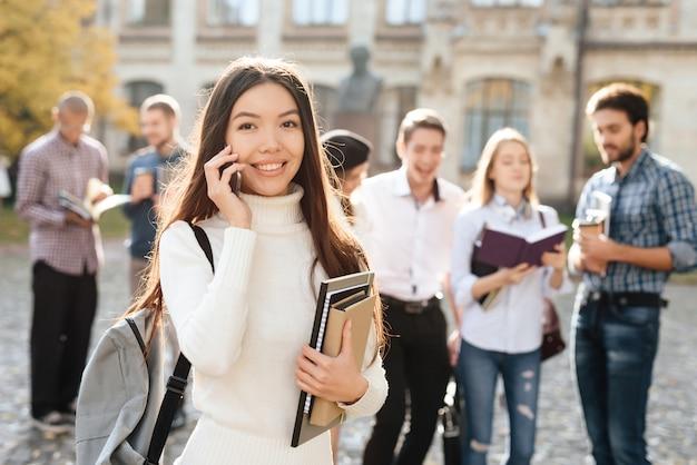 La fille asiatique est debout avec le téléphone.
