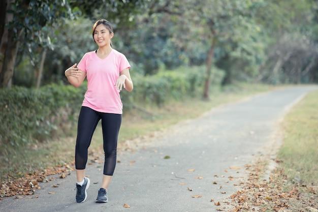 Fille asiatique étire ses muscles chauds du corps avant de sortir courir au parc