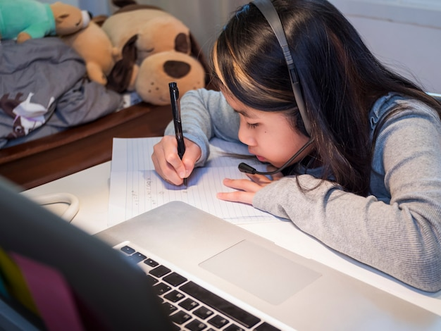 Une fille asiatique étudie en ligne avec un ordinateur portable l'enfant porte un casque d'écriture dans un cahier d'apprentissage à l'aide de cours sur internet en quarantaine l'élève apprend avec une classe en ligne sur internet de l'école covid19