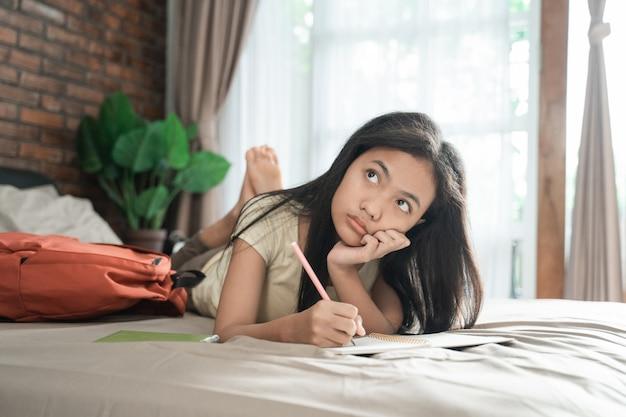 Fille asiatique étudie et pense sur le lit