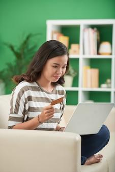 Fille asiatique faisant des commandes en ligne sur un ordinateur portable