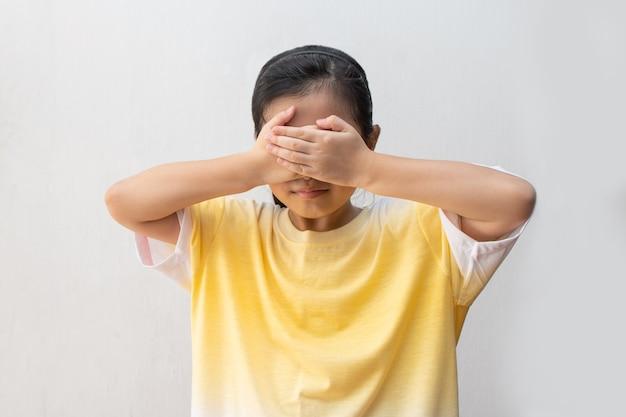 Fille asiatique a fermé les yeux avec ses mains